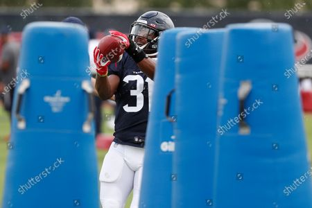 Houston Texans running back David Johnson makes a catch between a set of blocking dummies during an NFL training camp football practice, in Houston
