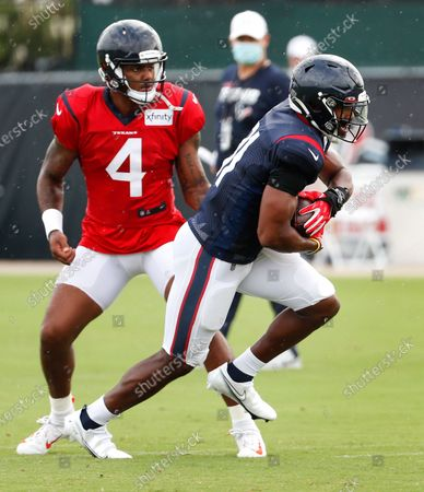 Houston Texans quarterback Deshaun Watson (4) hands the ball off to running back David Johnson (31) during an NFL training camp football practice, in Houston