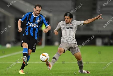 Inter Milan's Diego Godin, left, challenges for the ball with Shakhtar's Taison during the Europa League semifinal soccer match between Inter Milan and Shakhtar Donetsk at Dusseldorf Arena, in Duesseldorf, Germany