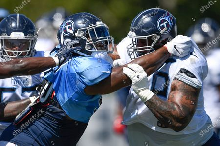 Tennessee Titans guard Rodger Saffold III, right, battles with defensive tackle Isaiah Mack during NFL football training camp, in Nashville, Tenn
