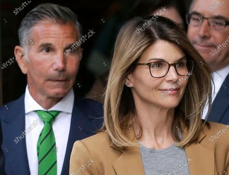 Actress Lori Loughlin, front, and husband, clothing designer Mossimo Giannulli, left, depart federal court in Boston after facing charges in a nationwide college admissions bribery scandal. The famous couple pleaded guilty to charges in May 2020, and are scheduled to be sentenced on