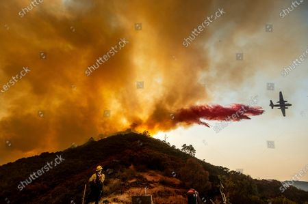 Stock Picture of Firefighter Ian Johnson watches as an air tanker drops retardant to keep the River Fire from reaching a home in Salinas, Calif., on . Fire crews across the region scrambled to contain dozens of blazes sparked by lightning strikes as a statewide heat wave continues