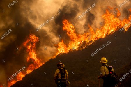 Flames from the River Fire crest a ridge as firefighters Ian Johnson, right, and Capt. Mike Campbell protects a home in Salinas, Calif., on . Fire crews across the region scrambled to contain dozens of blazes sparked by lightning strikes as a statewide heatwave continues