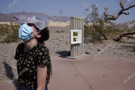 Katie Moore cools off with a bag of ice on her head, in Death Valley National Park, Calif. Death Valley recorded a scorching 130 degrees (54.4 degrees Celsius) Sunday, which if the sensors and other conditions check out, would be the hottest Earth has been in more than 89 years and the third-warmest ever measured