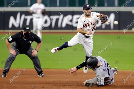 Houston Astros second baseman Jose Altuve (27) jumps to avoid the slide into second base by Colorado Rockies Trevor Story (27) as he turns a double play as umpire Bill Miller, left, looks on during the sixth inning of a baseball game, in Houston