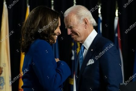 In this, Democratic presidential candidate former Vice President Joe Biden and his running mate Sen. Kamala Harris, D-Calif., pass each other as Harris moves tot the podium. To speak during a campaign event at Alexis Dupont High School in Wilmington, Del.. The Democratic Party's attempt to adapt its typical convention rituals to a pandemic-induced virtual affair will be put through its paces Tuesday night