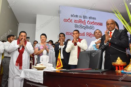 Stock Photo of Namal Rajapaksa (C), the eldest son of Sri Lanka's Prime Minister Mahinda Rajapaksa (L), prays before assuming duties as the country's new Minister of Sports and Youth Affairs, with his mother Shiranthi Rajapaksa (2nd L) in Colombo.