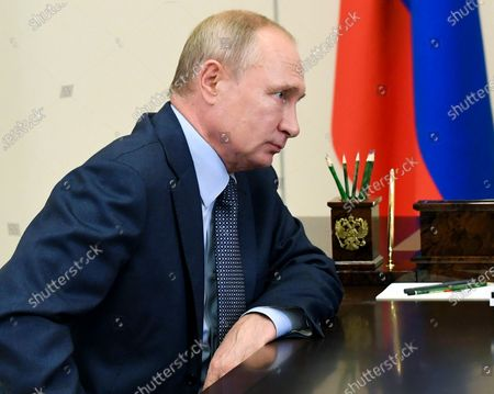 Russian President Vladimir Putin listens to Russian CEO of Rosneft oil company Igor Sechin during their meeting at the Novo-Ogaryovo residence outside Moscow, Russia