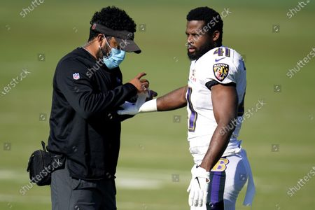 Baltimore Ravens staff member wears a face mask to protect against COVID-19 while putting tape on the wrist of safety Anthony Levine Sr. during an NFL football camp practice, in Owings Mills, Md