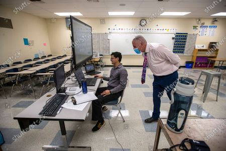 El Camino Real Charter High School Executive Director David Hussey, right, looks in on Spanish teacher Manuel Velarde's Spanish 2 class virtually taught from his classroom Tuesday, Aug. 11, 2020 in Woodland Hills, CA. (Brian van der Brug / Los Angeles Times)