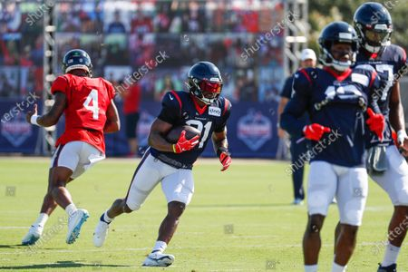 Houston Texans running back David Johnson (31) takes a handoff from quarterback Deshaun Watson (4) during practice at NFL football training camp, in Houston