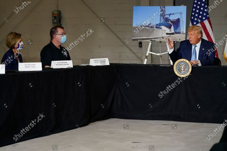 Iowa Gov. Kim Reynolds, left, and Federal Emergency Management Agency Administrator Peter Gaynor, center, listen as President Donald Trump speaks during a briefing on Iowa flood damage and recovery efforts, in Cedar Rapids, Iowa