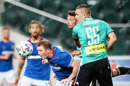 Shayne Lavery (L) of Linfield FC in action against Legia players Mateusz Wieteska (C) and Artur Jedrzejczyk (R) during the UEFA Champions League first qualifying round soccer match between Legia Warsaw and Linfield FC in Warsaw, Poland, 18 August 2020.