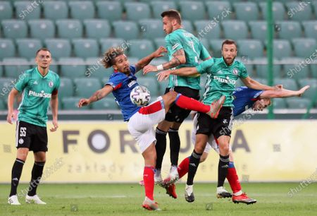 Legia players Artur Jedrzejczyk (L), Tomas Pekhart (C), and Domagoj Antolic (2-R) in action against Linfield players Bastien Hery (2-L) and Shayne Lavery (R) during the UEFA Champions League first qualifying round soccer match between Legia Warsaw and Linfield FC in Warsaw, Poland, 18 August 2020.