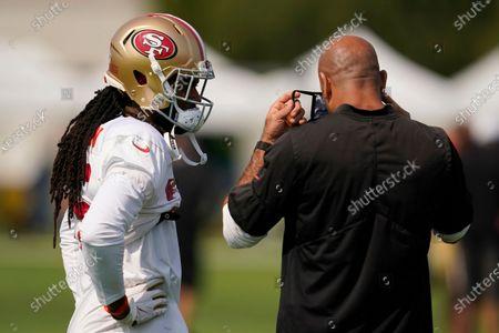 San Francisco 49ers defensive coordinator Robert Saleh, right, puts on a mask while talking with Richard Sherman during NFL football practice in Santa Clara, Calif