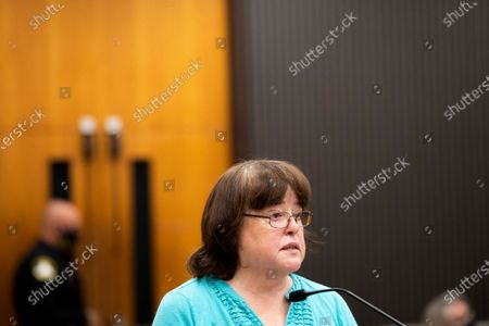 "Karen Veilleux reads a statement at the podium as Joseph James DeAngelo is in the court room during the first day of victim impact statements at the Gordon D. Schaber Sacramento County Courthouse, in Sacramento, Calif. Veilleux spoke on behalf of her ill sister Phyllis Henneman, who was the first victim of DeAngelo's crime spree that terrorized the state. The scope of his crimes ""is simply staggering,"" prosecutors said in a court summary released Monday - 13 known murders and nearly 50 rapes between 1975 and 1986"