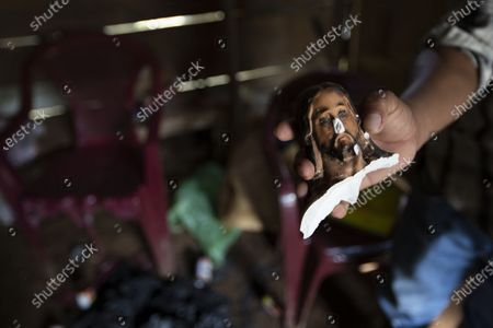 Julio Cesar Bol shows the head of a statue of Jesus that was decapitated during an attack inside his home that was partially burned by unidentified, armed men, on a coffee plantation in Cubilguitz, Guatemala, . Indigenous families have been living here for years as the result of a long-running labor dispute, and on Monday, President Alejandro Giammattei said the attackers had been identified