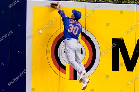 New York Mets right fielder Michael Conforto (30) can't get to a double hit by Miami Marlins' Matt Joyce during the fourth inning of a baseball game, in Miami
