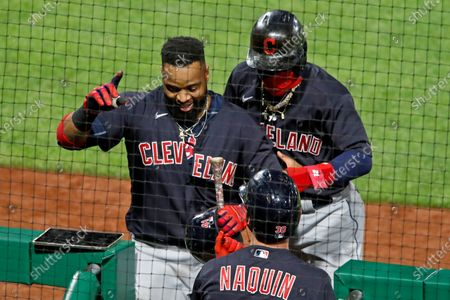 Cleveland Indians' Carlos Santana, left, returns to the dugout after hitting a three-run home run off Pittsburgh Pirates relief pitcher Sam Howard during the tenth inning of a baseball game against the Pittsburgh Pirates in Pittsburgh