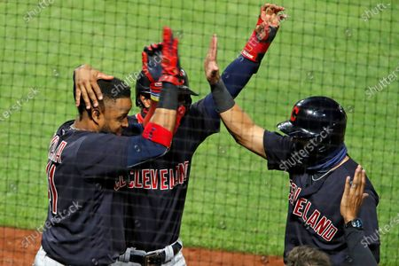 Cleveland Indians' Carlos Santana, left, celebrates with Francisco Lindor, center, and Cesar Hernandez, who were on base for his three-run home run off Pittsburgh Pirates relief pitcher Sam Howard during the tenth inning of a baseball game against the Pittsburgh Pirates in Pittsburgh
