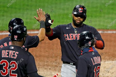 Cleveland Indians' Carlos Santana, top right, is greeted as he returns to the dugout after hitting a three-run home run off Pittsburgh Pirates relief pitcher Sam Howard during the 10th inning of a baseball game against the Pittsburgh Pirates in Pittsburgh, . The Indians won 6-3
