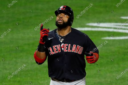 Cleveland Indians' Carlos Santana crosses home plate after hitting a three-run home run off Pittsburgh Pirates relief pitcher Sam Howard during the tenth inning of a baseball game against the Pittsburgh Pirates in Pittsburgh