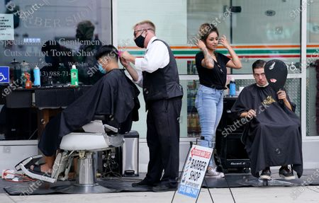 Stock Photo of Hair stylists Dan Tanner, second from left, and Yudi Hernandez, second from right, give haircuts to clients Alex Chang, left, and Tyler Beaubien outside Angelo's Barbershop, in the Little Tokyo section of Los Angeles