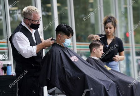 Hair stylists Dan Tanner, far left, and Yudy Hernandez, far right, give haircuts to clients Alex Chang, second from left, and Tyler Beaubien outside Angelo's Barbershop, in the Little Tokyo section of Los Angeles. Some salons and barbers have moved outdoors to comply with California's COVID-19 public health orders