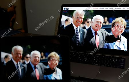 Former United States Senator John McCain of Arizona (C) and Democratic presidential nominee Joe Biden (L) are displayed on a computer during a friendship video for the virtual Democratic National Convention, in New York City, 18 August 2020.