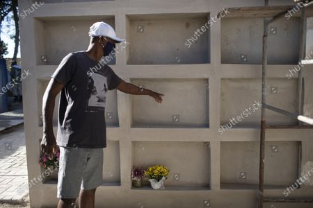"Eduardo Oliveira Costa, 49, points to the unmarked niche of his mother Carivaldina Oliveira da Costa, or ""Aunt Uia"", after she was recently buried at the Sant'Anna cemetery in Buzios, Brazil, one month after her June 10 death. Carivaldina Oliveira da Costa was the matriarch of the Rasa quilombo on the northern coast of Rio de Janeiro state. The woman known as Tia Uia has often been described as a ""living library"" - the keeper of the community's stories and customs who could recall the days before Buzios became an elite seaside getaway, and who fought for the rights of those living in quilombos. She died of COVID-19 last month, aged 78"