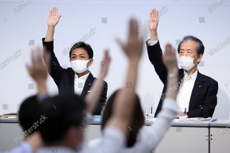 Stock Image of Japan's opposition Democratic Party for the People leader Yuichiro Tamaki (L), Secretary General Hirofumi Hirano (R) and party members raise their hands for a vote at the party's lawmakers meeting in Tokyo on Wednesday, August 19, 2020. Democratic Party for the People decided to merge  with another opposition Constitutional Democratic Party of Japan but Tamaki will not join the new party.