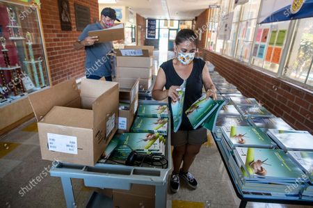 Patrick Henry Middle School special education assistants Carolyn Martinez, right, and husband Javier Martinez, left, unpack books for distribution as the beginning of the school year gets underway Tuesday, Aug. 18, 2020 in Granada Hills, CA. Brian van der Brug / Los Angeles Times)
