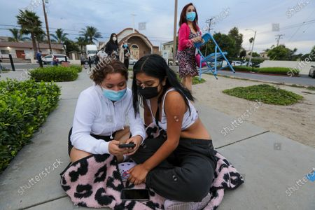 Angela Vasquez, 20, left, gives company to her friend Cynthia Rios, 20, who came to renew her license, waits in line for DMV facility to open for the day on Thursday, Aug. 13, 2020 in Westminster, CA. (Irfan Khan / Los Angeles Times)