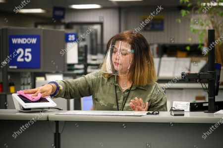 Gricelda Alba, sanitizes her station after serving a client at DMV on Thursday, Aug. 13, 2020 in Westminster, CA. (Irfan Khan / Los Angeles Times)