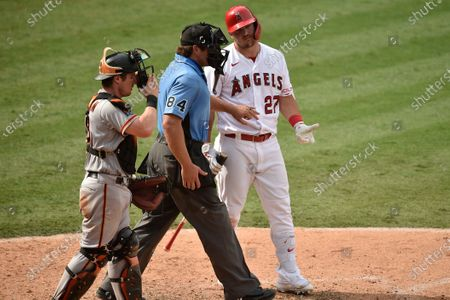 Los Angeles Angels' Mike Trout reacts after a pitch by San Francisco Giants pitcher Shaun Anderson as home plate umpire John Libka walks to the pitchers mound in front of Tyler Heineman during the ninth inning of a baseball game in Anaheim, Calif., . The Giants won 8-2