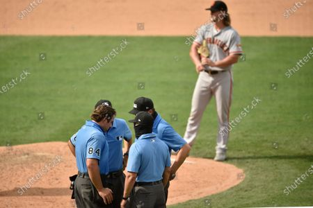 Umpires John Libka, Jim Reynolds, Lance Barrett and Adam Hamari discuss a pitch by San Francisco Giants starting pitcher Shaun Anderson during the ninth inning of a baseball game against the Los Angeles Angels in Anaheim, Calif., . The Giants won 8-2