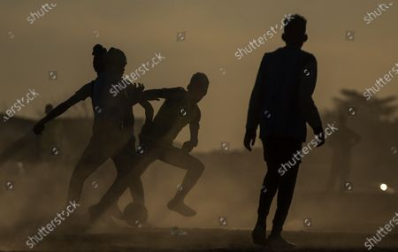 Young man play soccer on a dusty field in Soweto, South Africa, . South African president Cyril Ramaphosa announced that the entire country move to lockdown alert level 2 from Tuesday