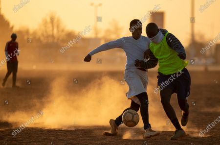 People plays soccer on a dusty field in Soweto, South Africa, . South African president Cyril Ramaphosa announced that the entire country move to lockdown alert level 2 from Tuesday