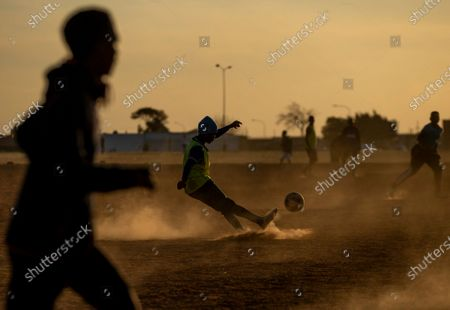 Young men play soccer on a dusty field in Soweto, South Africa, . South African president Cyril Ramaphosa announced that the entire country move to lockdown alert level 2 from Tuesday