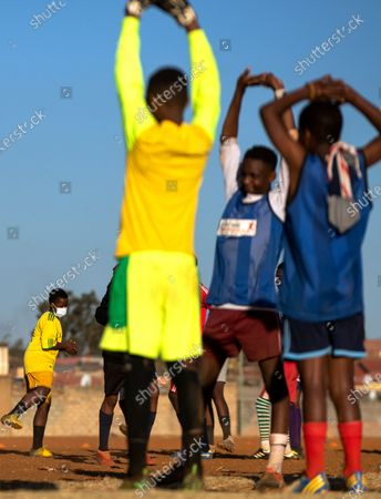 Young men stretches for their soccer training on a dusty field in Soweto, South Africa, . South African president Cyril Ramaphosa announced that the entire country move to lockdown alert level 2 from Tuesday