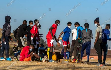 Young men prepare for their soccer training on a dusty field in Soweto, South Africa, . South African president Cyril Ramaphosa announced that the entire country move to lockdown alert level 2 from Tuesday