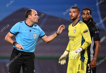 Referee Antonio Mateu Lahoz, left, discusses with Lyon's goalkeeper Anthony Lopes, centre, and Lyon's Jason Denayer during the Champions League semifinal soccer match between Lyon and Bayern at the Jose Alvalade stadium in Lisbon, Portugal
