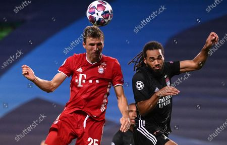 Bayern's Thomas Mueller, left, jumps for the ball with Lyon's Jason Denayer during the Champions League semifinal soccer match between Lyon and Bayern at the Jose Alvalade stadium in Lisbon, Portugal