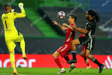 Bayern Munich's Robert Lewandowski (C) in action against Olympique Lyon's goalkeeper Anthony Lopes (L) and Jason Denayer (R) during the UEFA Champions League semi final soccer match between Olympique Lyon and Bayern Munich in Lisbon, Portugal, 19 August 2020.