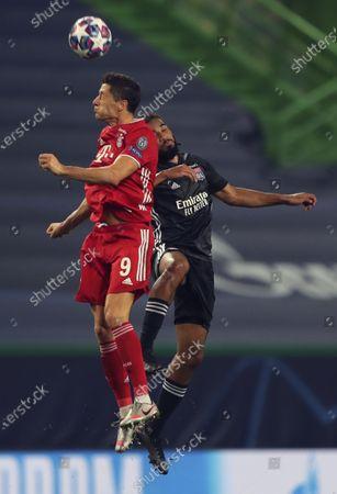 Bayern's Robert Lewandowski, left, and Lyon's Jason Denayer jump for the ball during the Champions League semifinal soccer match between Lyon and Bayern Munich at the Jose Alvalade stadium in Lisbon, Portugal