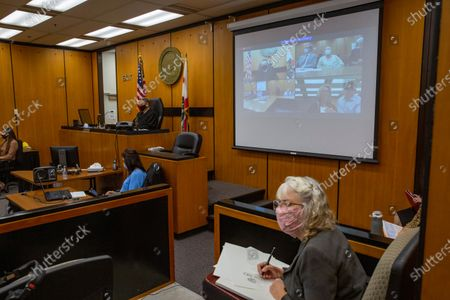 Gay Hardwick with her spouse Robert Hardwick are projected in the fourth quadrant on the projection screen behind a courtroom sketch artist, during the second day of victim impact statements with Joseph James DeAngelo present, second quadrant, at the Gordon D. Schaber Sacramento County Courthouse, in Sacramento, Calif. Victims of California serial killer and rapist, DeAngelo want him in a maximum security prison far, far away if he can't spend the rest of his life on death row. But they may not hold much sway over where or how the 74-year-old former police officer is imprisoned once he is sentenced on Friday, Aug. 21