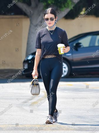 Lucy Hale is seen wearing an all black outfit with a leopard accent and carrying a cold drink