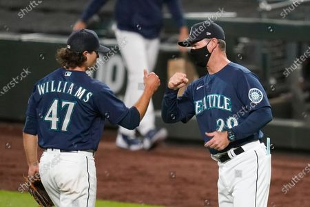 Seattle Mariners manager Scott Servais, right, greets closing pitcher Taylor Williams after the Mariners defeated the Los Angeles Dodgers 6-4 in a baseball game, in Seattle