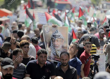 Palestinian protester holding a placard of Yasser Arafat during a demonstration against the agreement to establish diplomatic relations between Israel and the United Arab Emirates at the Jabalia refugee camp in the northern Gaza Strip.