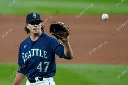 Seattle Mariners closing pitcher Taylor Williams reaches for a ball against the Los Angeles Dodgers in a baseball game, in Seattle